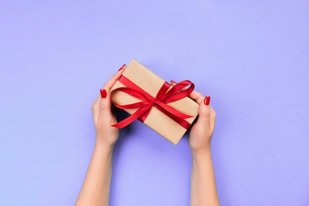 Frauenhände geben eingewickelten valentinsgruß oder anderes handgemachtes geschenk des feiertags im papier mit rotem band