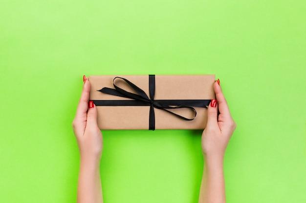 Frauenhände geben eingewickelten valentinsgruß oder anderes handgemachtes geschenk des feiertags im papier mit schwarzem band. präsentkarton, dekoration des geschenks auf grüner tabelle, draufsicht mit kopienraum