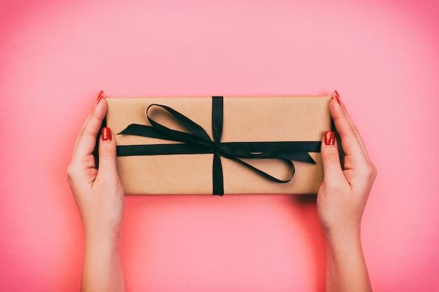 Frauenhände geben eingewickelten valentinsgruß oder anderes handgemachtes geschenk des feiertags im papier mit schwarzem band. präsentkarton, dekoration des geschenks auf korallenroter farbtabelle, draufsicht