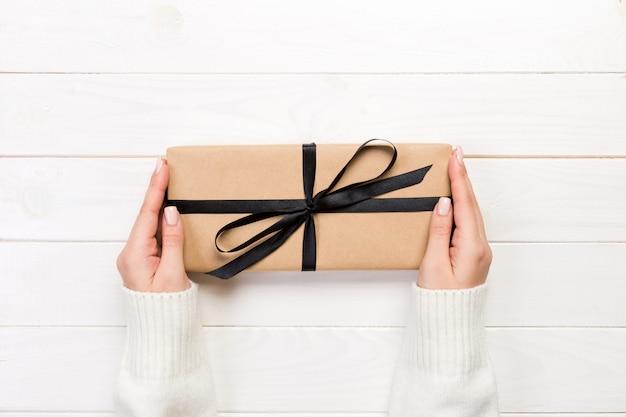 Frauenhände geben eingewickelten valentinsgruß oder anderes handgemachtes geschenk des feiertags im papier mit schwarzem band.