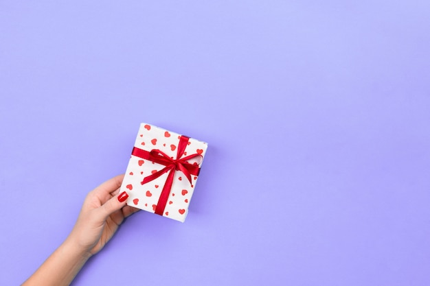 Frauenhände geben eingewickelten valentinsgruß oder anderes handgemachtes geschenk des feiertags im papier