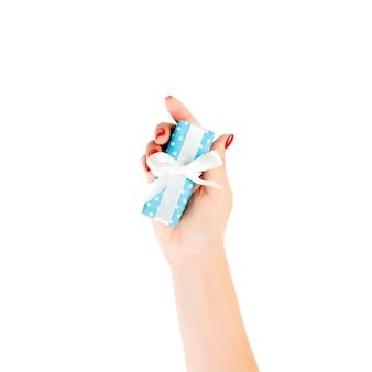 Frauenhände geben eingewickeltes geschenk in blauem papier mit weißem band. isoliert auf weißer oberfläche, draufsicht.