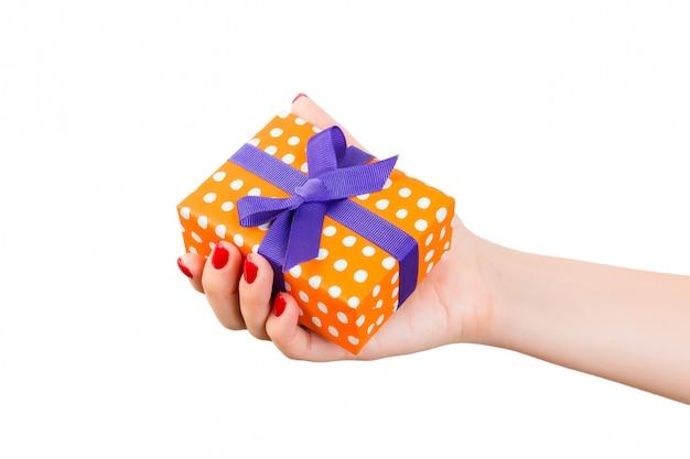 Frauenhände geben eingewickeltes weihnachten oder anderes handgemachtes geschenk des feiertags im orange papier mit purpurrotem band