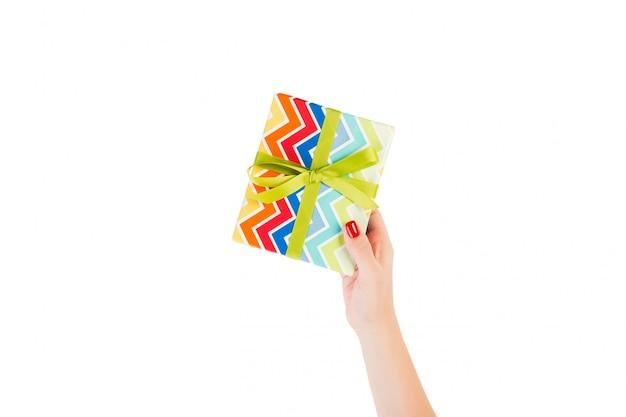 Frauenhände geben eingewickeltes weihnachten oder anderes handgemachtes geschenk des feiertags in farbigem papier mit grünem band. isoliert auf weiss