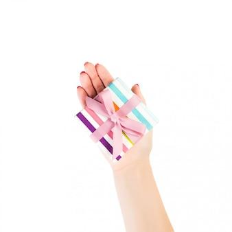 Frauenhände geben eingewickeltes weihnachten oder anderes handgemachtes geschenk des feiertags in farbigem papier mit rosa band. isoliert auf weiss