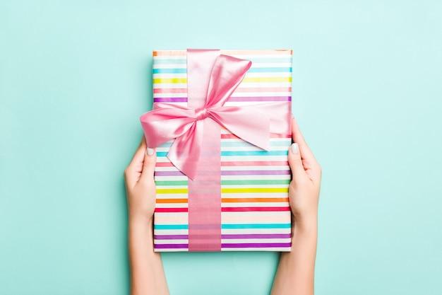 Frauenhände geben eingewickeltes weihnachten oder anderes handgemachtes geschenk des feiertags in farbigem papier. präsentkarton, dekoration des geschenks auf blauer tabelle, draufsicht
