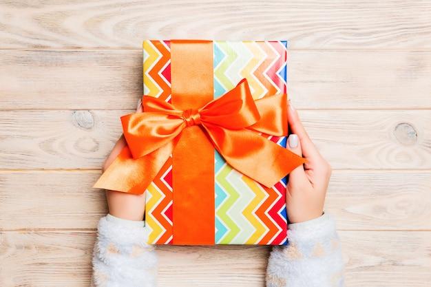 Frauenhände geben eingewickeltes weihnachten oder anderes handgemachtes geschenk des feiertags in farbigem papier. präsentkarton, dekoration des geschenks auf gelbem rustikalem holztisch, draufsicht mit kopienraum