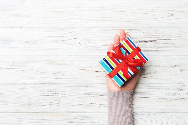 Frauenhände geben eingewickeltes weihnachten oder anderes handgemachtes geschenk des feiertags in farbigem papier. präsentkarton, dekoration des geschenks auf weißem rustikalem holztisch, draufsicht mit kopienraum