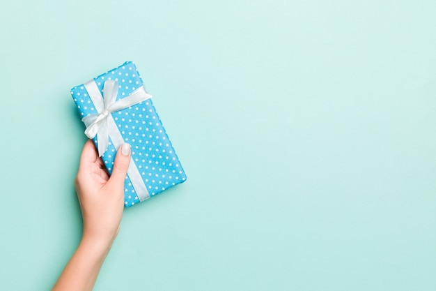 Frauenhände geben eingewickeltes weihnachten oder anderes handgemachtes geschenk des feiertags in farbigem papier