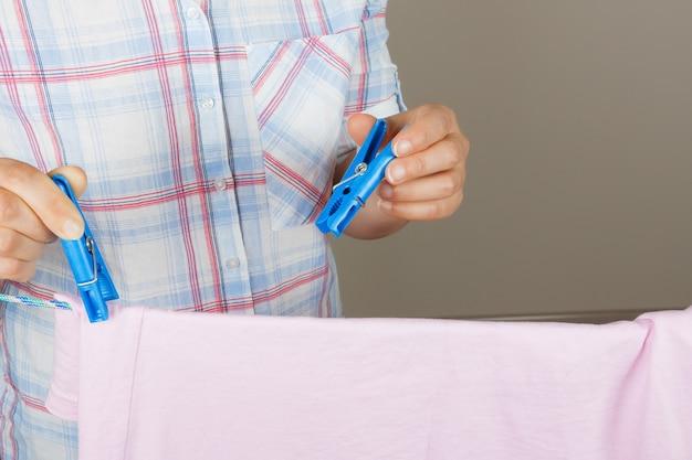 Frauenhände hängen nasses sauberes tuch zum trocknen auf der wäscheleine in der waschküche auf grauem hintergrund