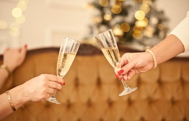 Frauenhände halten die gläser champagner und machen einen toast. weihnachten feiern konzept.