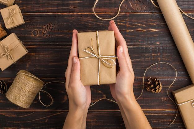 Frauenhände halten ein geschenk des kraftpapiers.