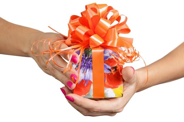 Frauenhände halten ein geschenk nah oben auf dem weißen hintergrund isoliert
