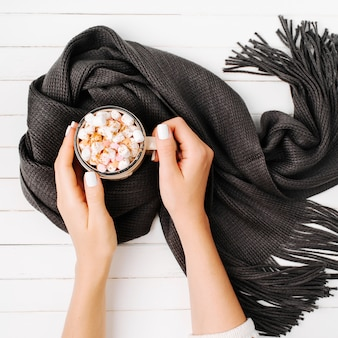 Frauenhände halten eine tasse kaffee in schal auf holzhintergrund gewickelt. herbst- oder winterkonzept. flach liegend, ansicht von oben