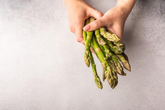 Frauenhände halten einen bund frischen grünen spargel