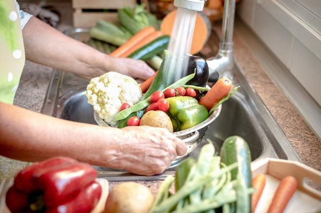 Frauenhände halten einen korb mit gemüse unter fließendem wasser, um sie zu waschen