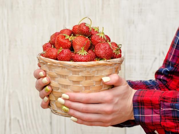 Frauenhände halten einen weidenkorb mit reifen erdbeeren auf hellem holz