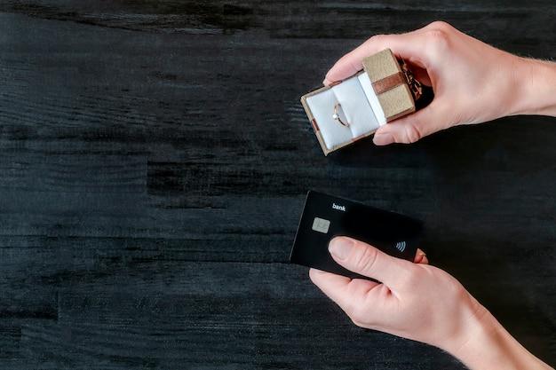 Frauenhände halten geschenkbox mit goldenem ring und kreditkarte auf schwarzem holztisch. kauf von geschenk, schmuck, finanzen, geld, bankkonzept, draufsicht, kopienraum