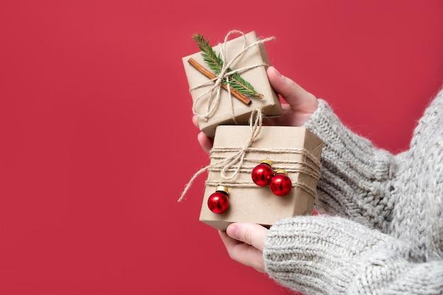 Frauenhände halten geschenkboxen aus kraftpapier mit weihnachtsdekor auf rotem grund, nahaufnahme. hintergrund des neuen jahres. geschenkverpackungen aus naturmaterialien im retro-, vintage-, trend-stil.