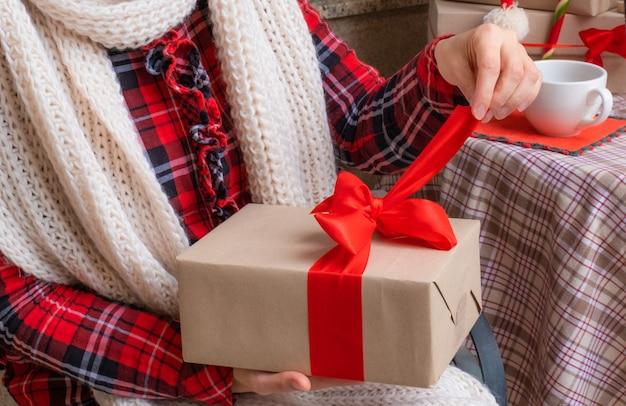 Frauenhände halten geschenke am vorabend der feiertage weihnachten und neujahr