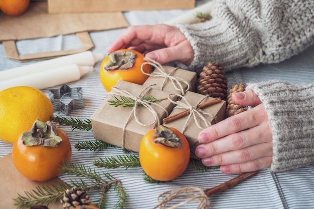 Frauenhände halten geschenke für das neue jahr. weihnachtshintergrund mit geschenkboxen, kegeln, weihnachtsbaum und persimone, draufsicht, nahaufnahme. handgemachtes geschenk.