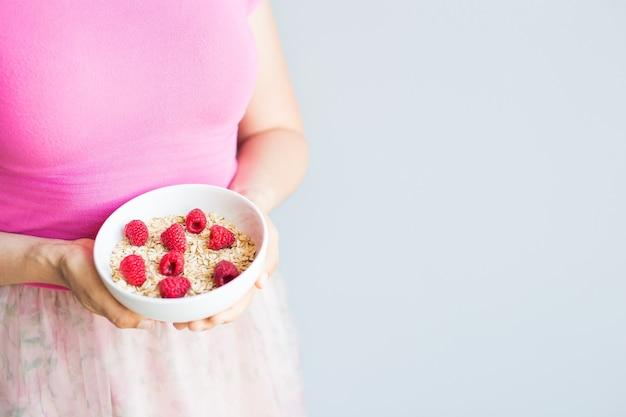 Frauenhände halten gesundes und natürliches frühstück, haferflocken und himbeeren in einer schüssel.