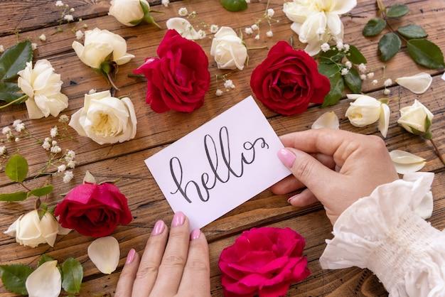 Frauenhände halten hallo-karte in der nähe von blumen auf einem holztisch aus nächster nähe