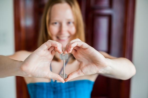 Frauenhände halten hausschlüssel in form des herzens auf dem hintergrund eine holztür. immobilienkonzept besitzen