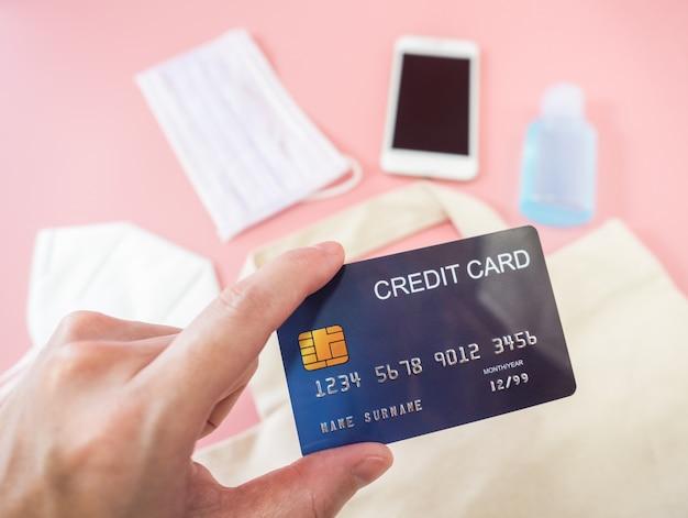 Frauenhände halten kreditkarten mit smartphone, op-maske, kreditkarte und alkohol-gel-desinfektionsmittel auf blassrosa oberfläche. covid-19, coronavirus-, geschäfts- und finanzkonzept.