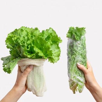 Frauenhände halten plastiktüte aus polyethylen und tasche aus umweltfreundlicher baumwolle. vergleichskonzept. plastikfrei, kein abfall. hellgrauer hintergrund mit kopierraum. grün, gemüse.