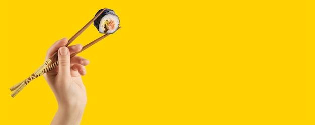 Frauenhände halten sushi-rollen mit stöcken. gelber hintergrund. kreatives konzept