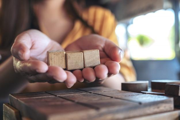 Frauenhände halten und zeigen drei quadratische holzklötze