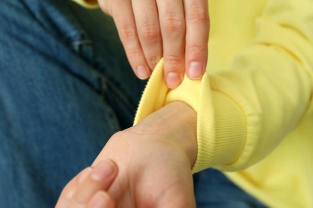 Frauenhände im gelben sweatshirt