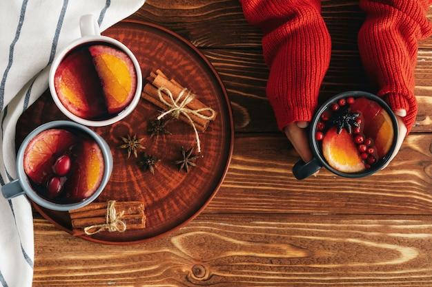 Frauenhände im warmen pullover, der eine tasse glühwein hält