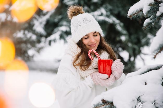 Frauenhände in den handschuhen, die einen gemütlichen becher mit heißem kakao, tee oder kaffee und einer zuckerstange halten.