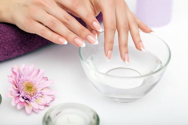 Frauenhände in einem nagelsalon, der ein handpeeling durch einen kosmetiker empfängt. spa maniküre, handmassage und körperpflege, spa-behandlungen. Premium Fotos