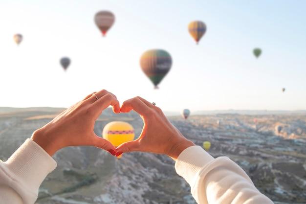 Frauenhände in form eines herzens vor dem hintergrund fliegender luftballons am himmel von kappadokien feiertage in der türkei reisen während einer pandemie