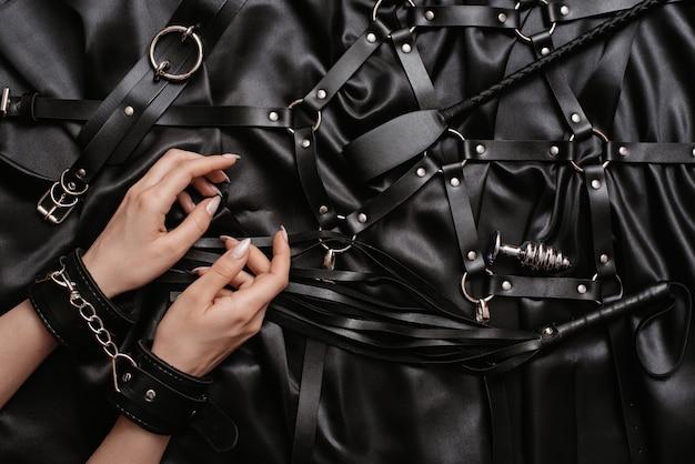 Frauenhände in handschellen auf einem dunklen seidenblatt neben spielzeug für erwachsene