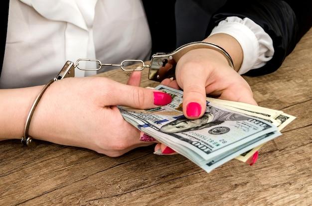 Frauenhände in handschellen mit dollars in den händen