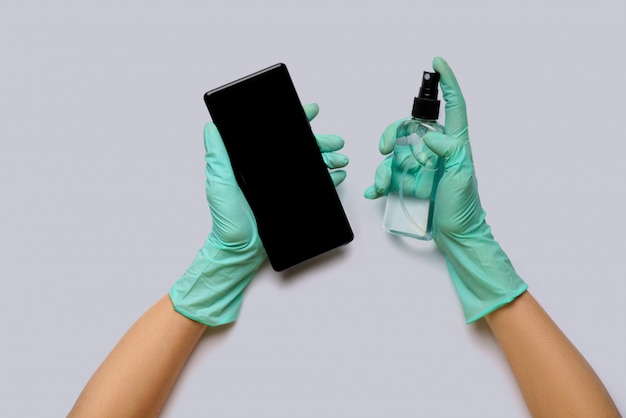 Frauenhände in latexhandschuhen, die handy mit alkoholdekontaminationsmittel-draufsicht über hellgrauem hintergrund abwischen
