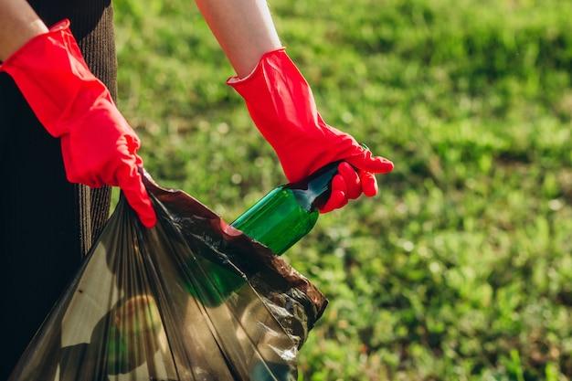 Frauenhände in roten gummihandschuhen. frau sammelt müll in der tasche. freiwilliger müll im sommerpark. mädchen sammelt plastik- und glasflaschen in der verpackung