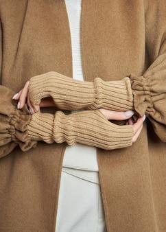Frauenhände in warmen winterhandschuhen. herbstkleidung. schöne nagelmaniküre