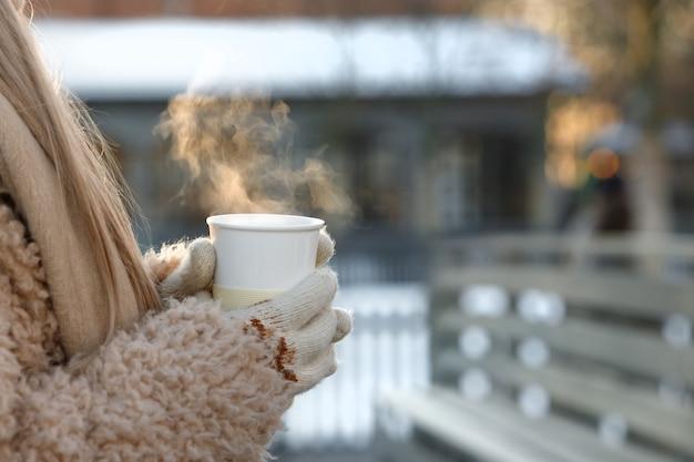 Frauenhände in weißen handschuhen, die dampfenden weißen tasse heißen kaffee oder tee im kalten winter sonnigen tag halten