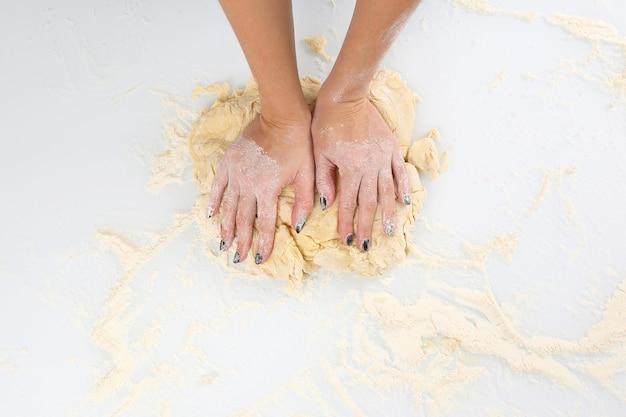 Frauenhände kneten den teig auf einem licht