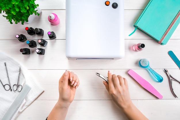 Frauenhände machen maniküre zu sich selbst auf hölzernem hintergrund. ansicht von oben. platz kopieren. nagelpflege.