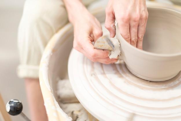 Frauenhände macht tongefäß auf der töpferscheibe