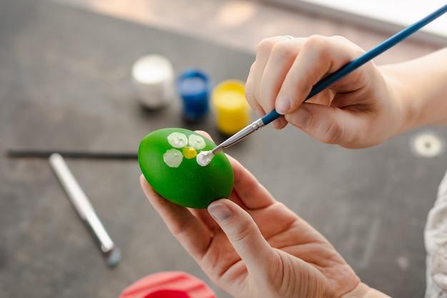 Frauenhände malen mit aquarellen auf dem ei, um ostereier vorzubereiten