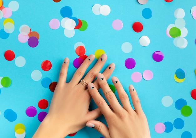 Frauenhände mit buntem konfetti über blauem hintergrund. beauty fashion spa salon konzept
