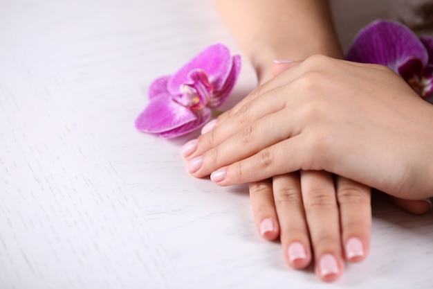 Frauenhände mit französischer maniküre und orchideenblumen auf hölzerner tischnahaufnahme