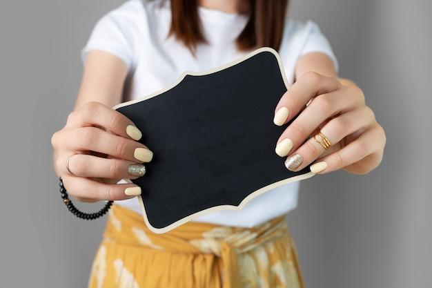 Frauenhände mit gelbem glänzendem nageldesign, das holzschild hält